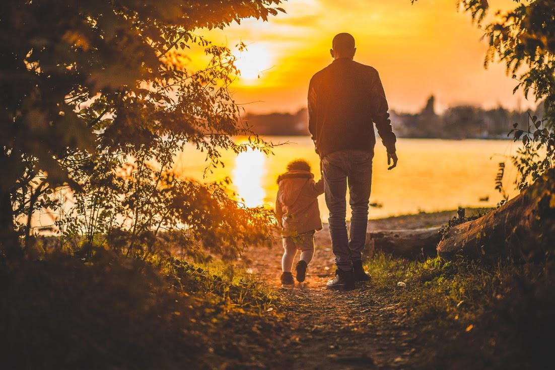 father and son in front of lake at sunset